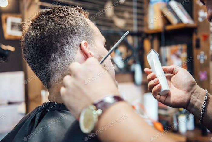 der Meister im Friseurladen rasiert und schneidet den Mann