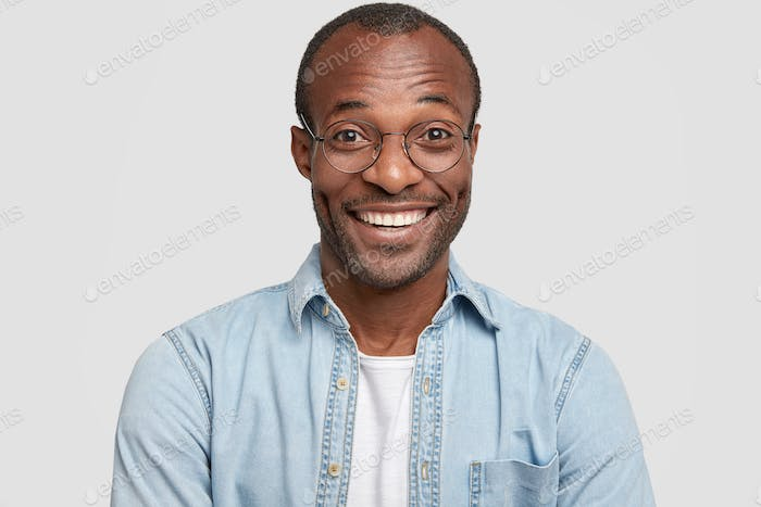 Portrait of happy cheerful dark skinned male laughs joyfully, works in restaurant, greets new visito