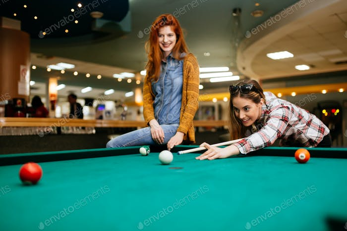 Two female friends playing snooker