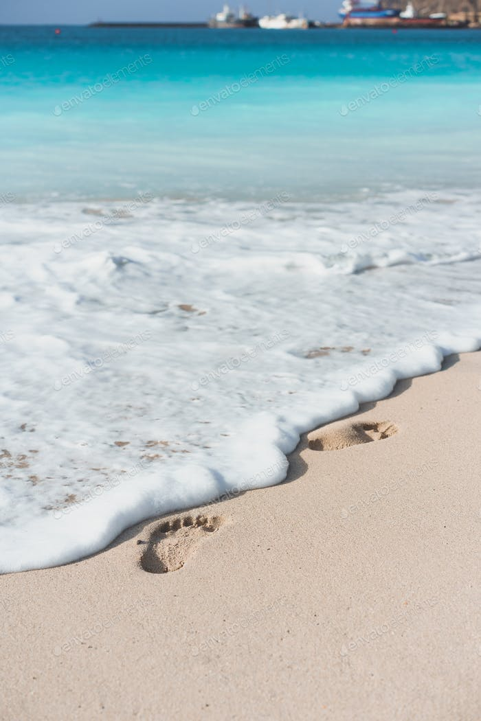 Ocean waves touching the foot prints on the tropical beach