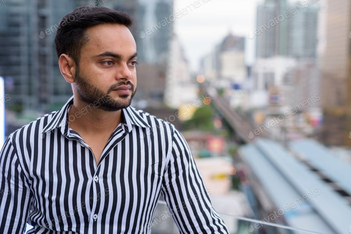Young bearded Indian businessman against view of the city