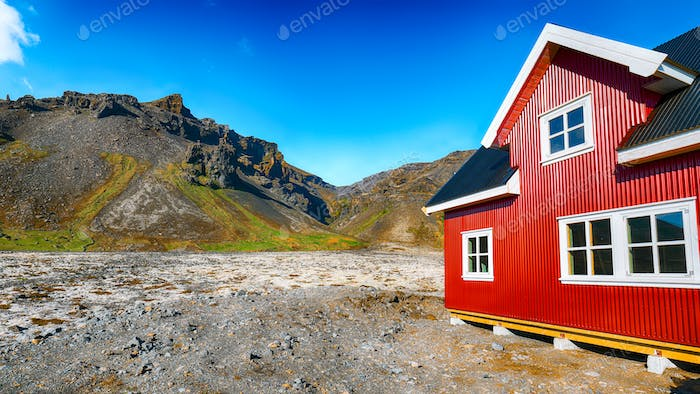 The charming rustic rural house on the mountains background in Icelandic landscape