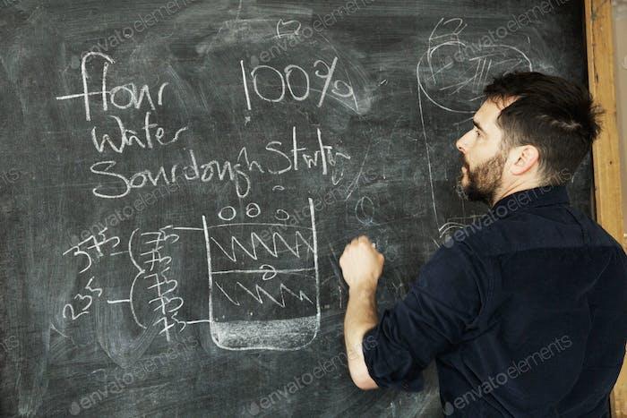 Baker steht vor einer Tafel und schreibt ein Rezept für Brot.
