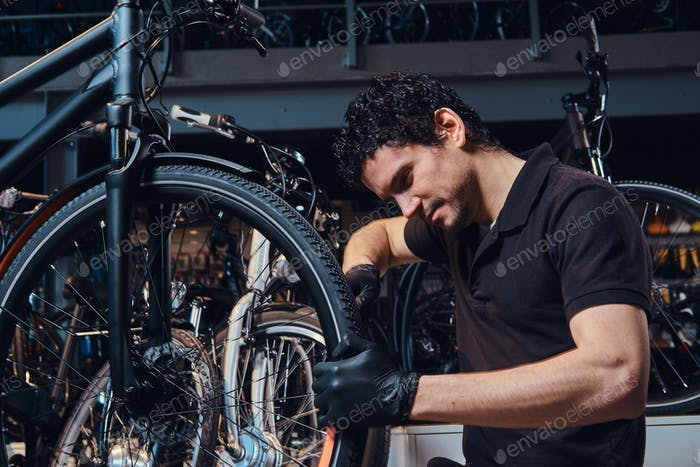 Diligent young mechanic is repairing customer's bicycle at workplace