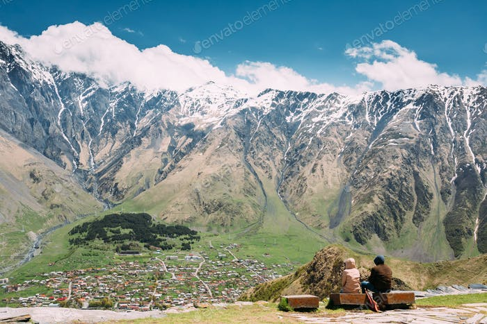 People Sitting Together On A Stone Bench Near The Gergeti Trinit