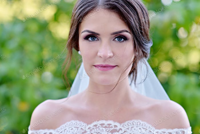 Beauty bride in bridal gown with lace veil in the nature
