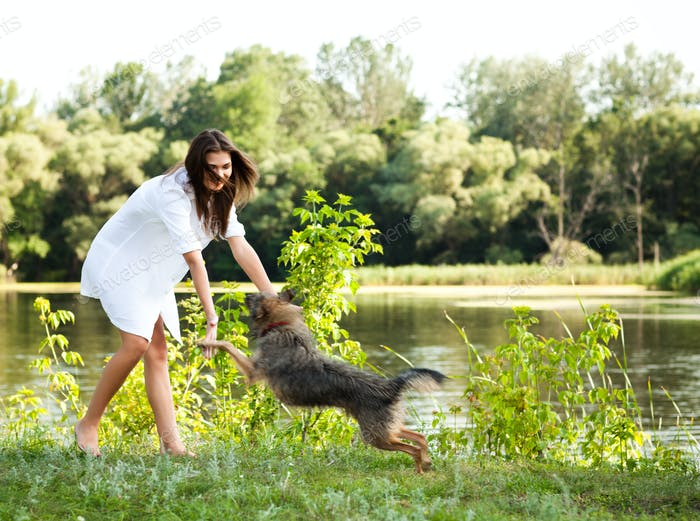Young brunette woman in white dress playing with dog on grass on summer day with green trees and