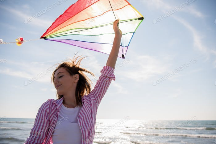 Young Woman with kite at beach on autumn day