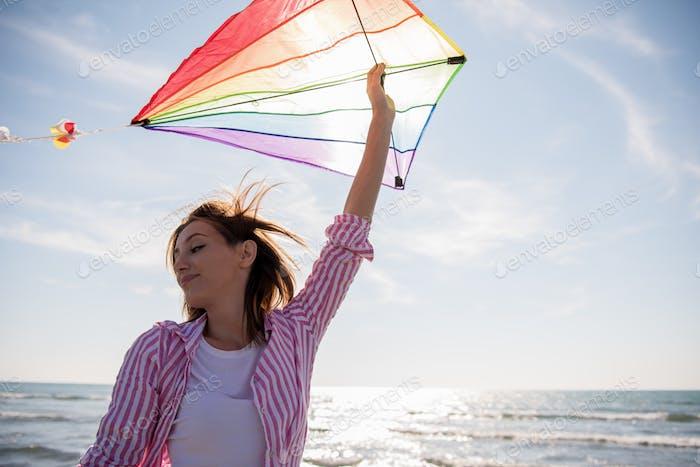 Junge Frau mit Drachen am Strand am Herbsttag