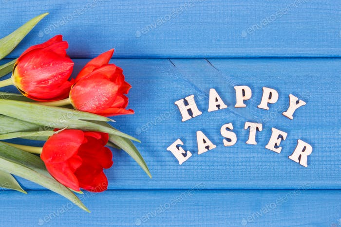 Inscription Happy Easter and red tulips on boards, festive decoration