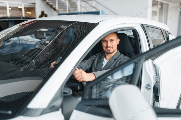 Man sitting in new car, showroom