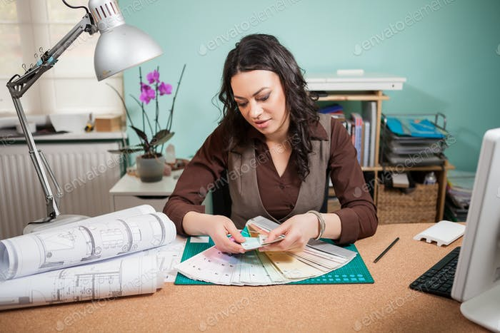 Architect woman in her office with color cards in front