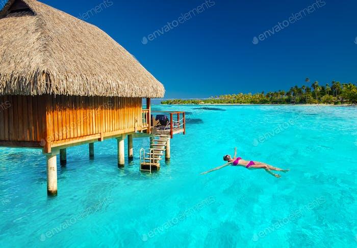 Junge Frau Schwimmen in tropischer Lagune neben Überwasser Villa