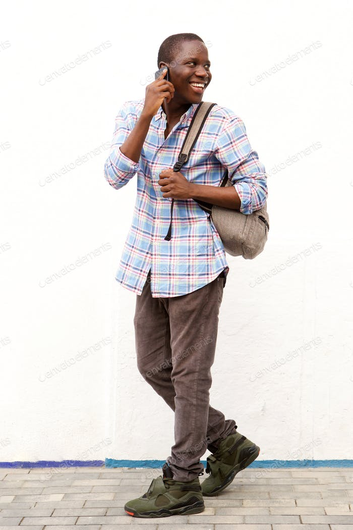 smiling african man walking outside and talking on cell phone