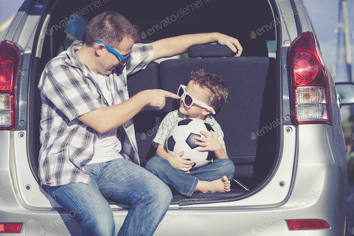 Happy father and son getting ready for road trip on a sunny day