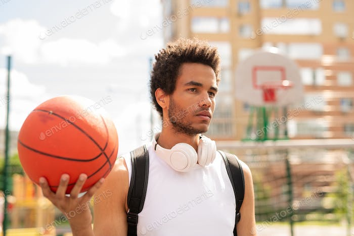 Serious active guy with ball standing on basketball court or playground