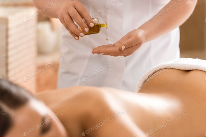 massage therapist making massage with body oil for woman in spa salon