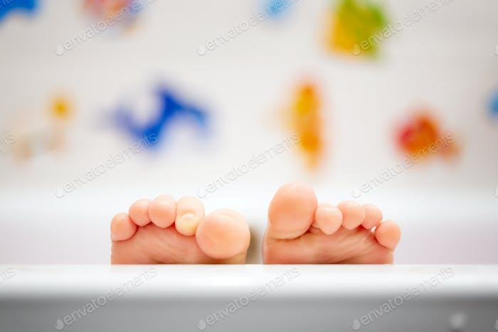 Baby in the bathroom. Detail of cute wet feet covered with warm water.