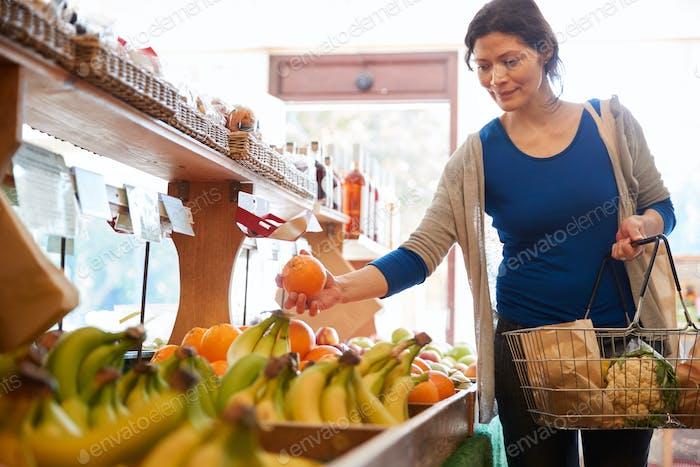 Female Customer With Shopping Basket Buying Fresh Oranges In Organic Farm Shop