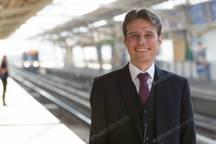 Portrait of happy businessman smiling at train station