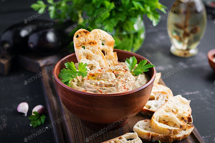 Baba ghanoush vegan hummus from eggplant with seasoning, parsley and toasts.