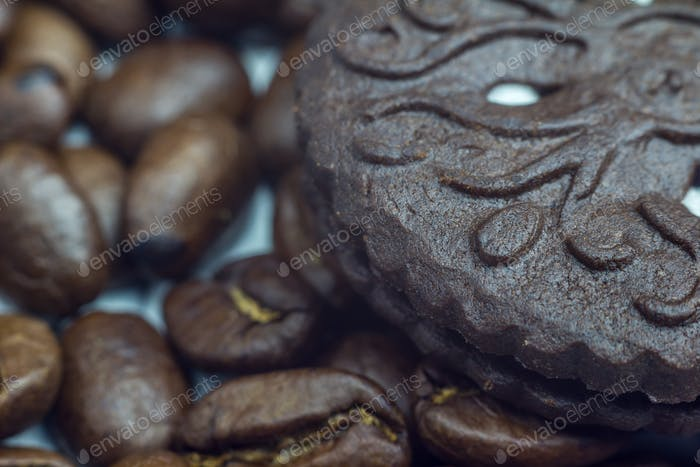 Coffee beans and chocolate cookie close up, selective focus