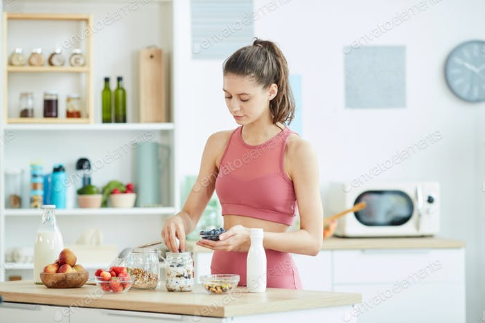 Sportive Young Woman Making Granola Dessert