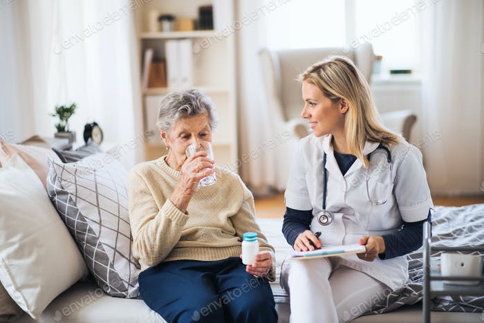 A health visitor and a senior woman at home, taking pills.