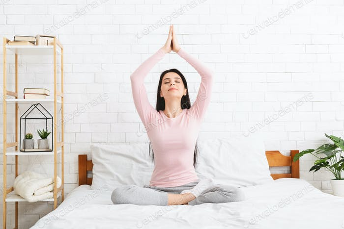 Young woman meditating in bed, free space