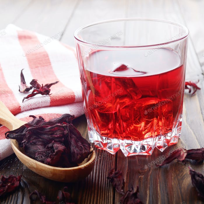 Closeup view at glass of tea with ice and spoon of dry hibiscus