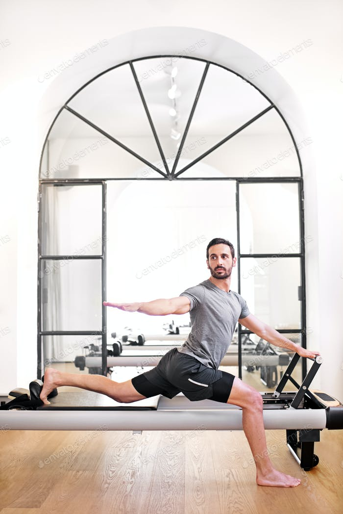 Man doing a standing pilates lunge stretch