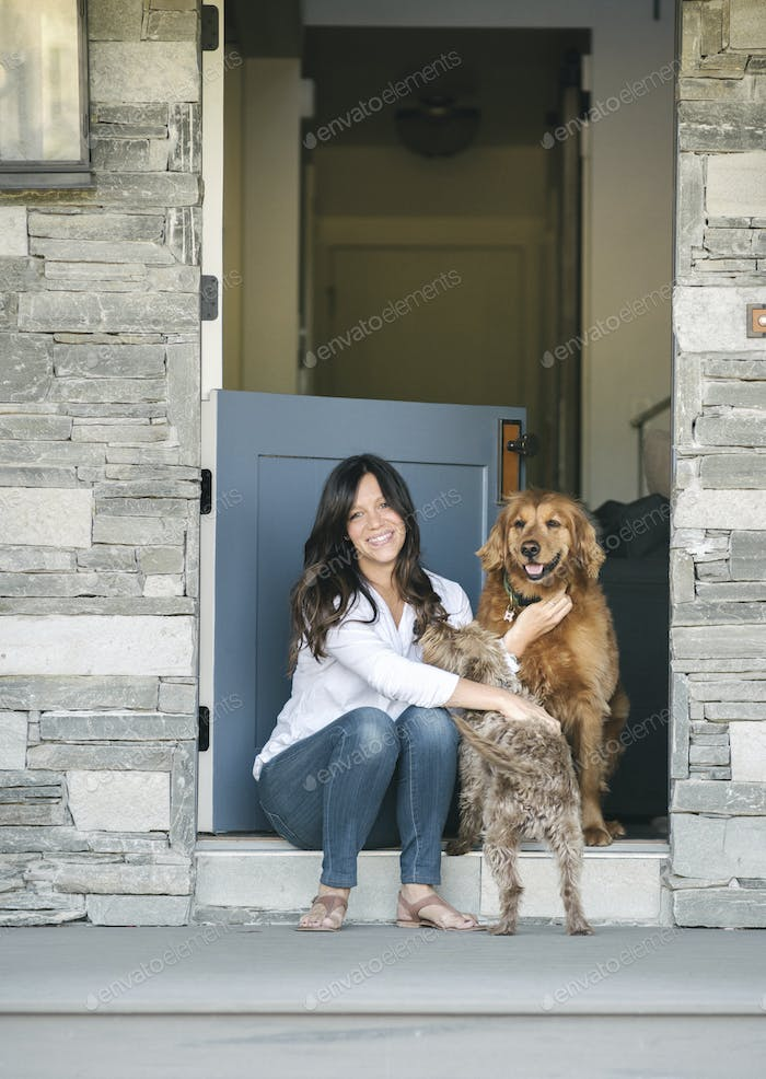 Woman sitting by her door patting her two dogs.