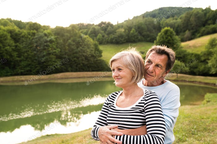 Senior couple on a walk at the lake hugging.