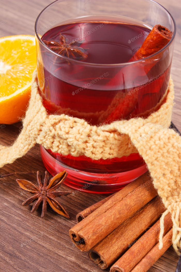 Glass of mulled wine wrapped scarf with fresh fragrant spices