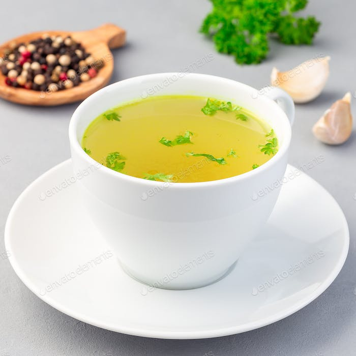 Chicken broth in white cup with chopped parsley, square format