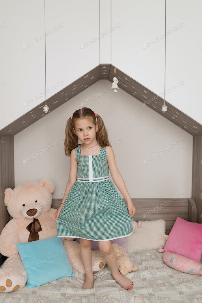 Lovely kid standing on the bed in her room