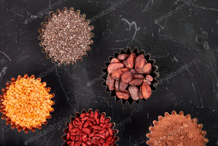 Various superfoods in small bowl on black background