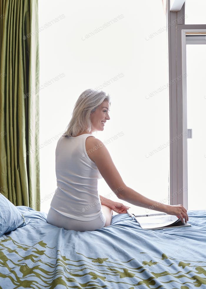 Mature Caucasian woman in her bedroom sitting on her bed looking at a magazine