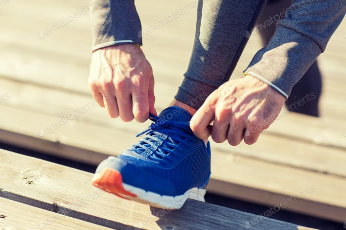 close up of sporty man tying shoe laces outdoors
