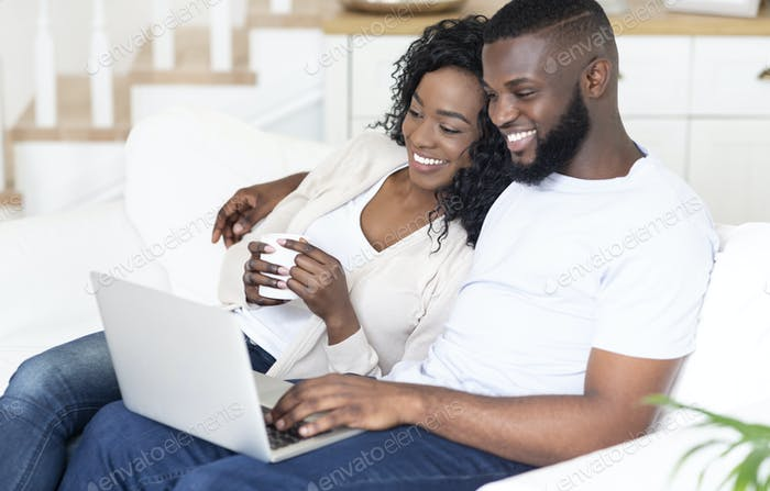 Happy African American man and woman enjoying movie on laptop