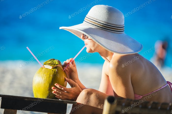 oung woman drinking coconut juice while relaxing on the beach