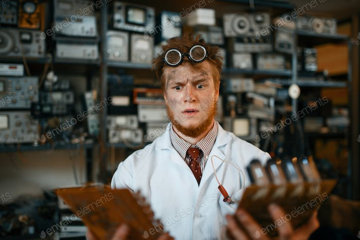 Strange engineer looks on electronic chips in lab