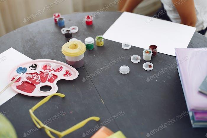 Kleines Mädchen sitzt auf einem Tisch und Zeichnung