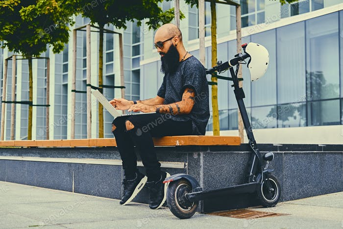 Bearded male using a laptop after electric scooter ride.