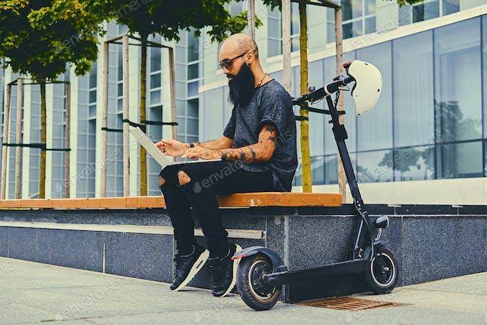 Varón barbudo usando un ordenador portátil después de montar en scooter eléctrico.