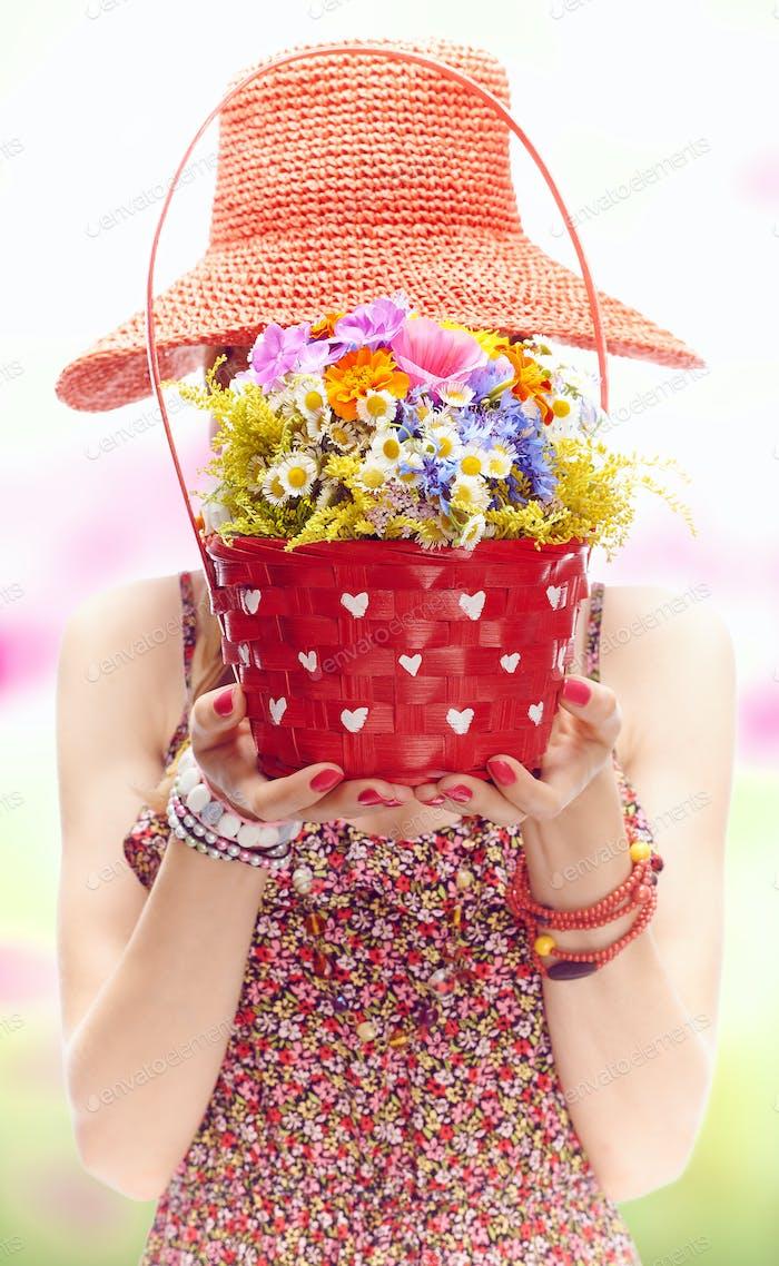 Frau auf Sommerwiese mit Korb von Wildblumen