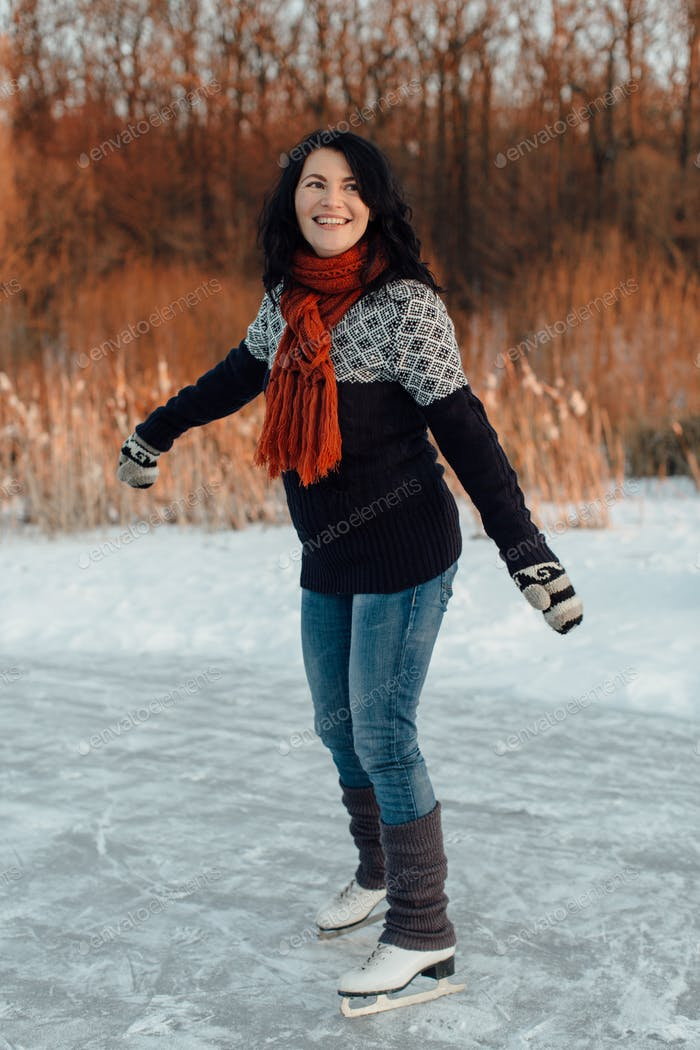 Happy woman learning to ice skate