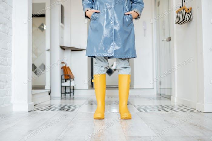 Frau in gelben Gummistiefeln und Regenmantel drinnen