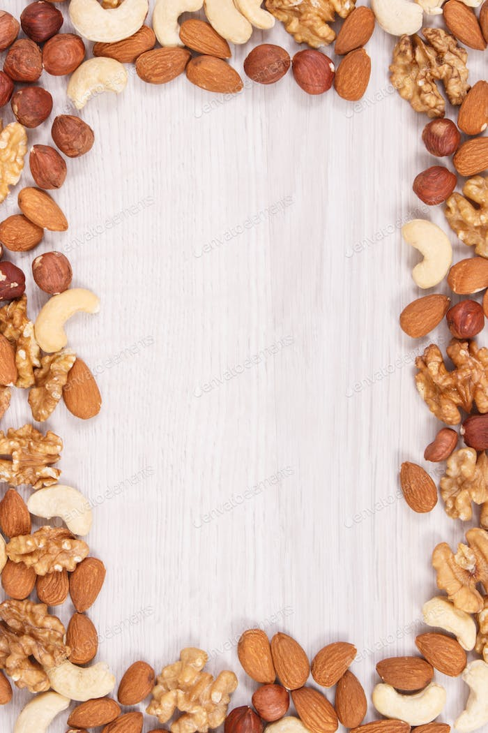 Frame of different nuts and almonds as source vitamins and minerals, copy space for text