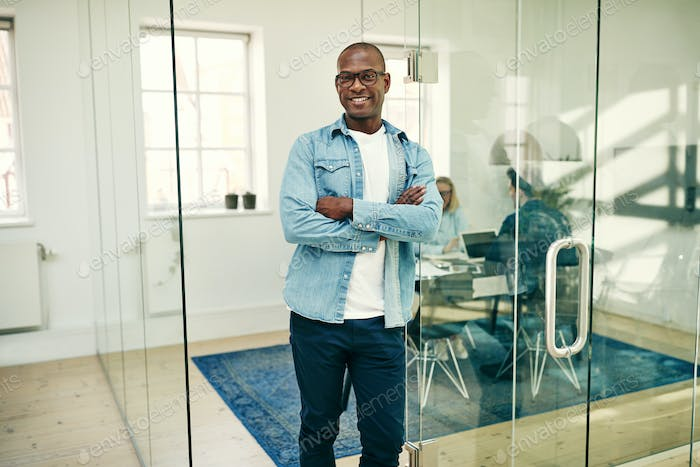 Confident African businessman standing with his arms crossed at work